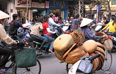 Laden cyclists and motorbikes compete for road space. Vietnam 2007. Photo by S. Chong-Purkiss