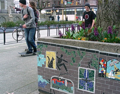 Urban life mosaics adorn a concrete city planter by the Dunsmuir separated bike lanes. Vancouver BC 2012. Photo by J.Chong