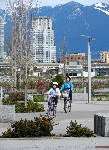 Cycling paths in Olympic Village are well-travelled most days at all hours. Background is city skyline and North shore mountains. Vancouver, BC 2012. Photo by J.Chong
