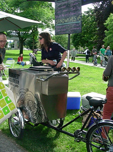 Ice cream sandwich vendor pedals her handmade  goodies by bike. Farmers' market by Vancouver railway station. 2012 Photo by J. Chong
