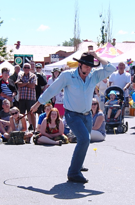 Cowboy entertainer just finished bull-whipping a dandelion flower from top his head.  Street performance was a month long after Stampede was over. Calgary AB 2013. Phot by J. Chong